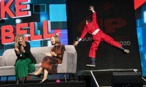 Two smiling women seated on a sofa and clapping on stage with a funny man stuck to a wall with arms and legs stretched out
