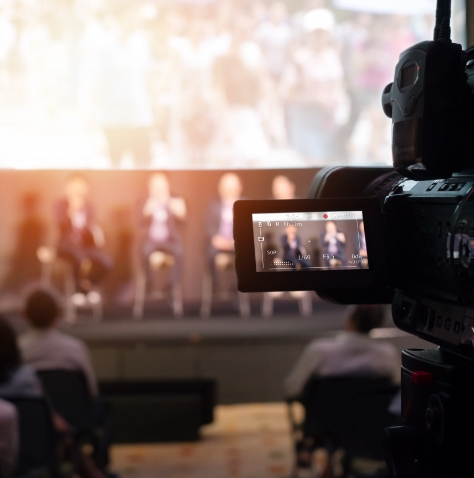 camera recording men on stage