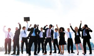 People in business attire cheering with raised arms and closed fists outdoors